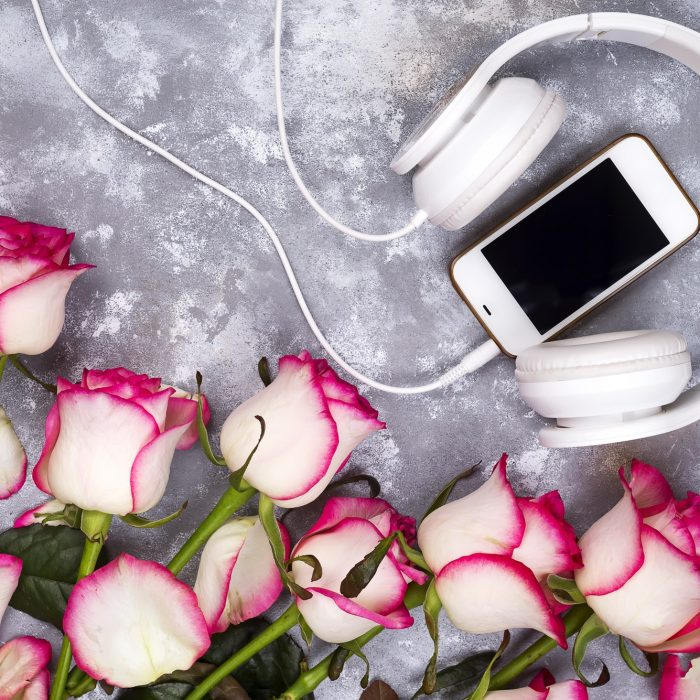 composed frame of the roses and mobile phone with headphones